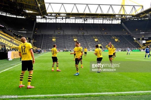 Dortmund's Norwegian forward Erling Braut Haaland celebrates with team players after scoring the opening goal during the German first division...