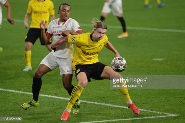Dortmund's Norwegian forward Erling Braut Haaland challenges Sevilla's French defender Jules Kounde during the UEFA Champions League round of 16...