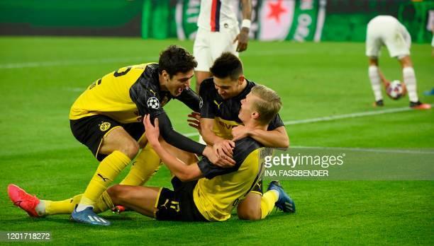 Dortmund's Norwegian forward Erling Braut Haaland is congratulated by his teammates Dortmund's US midfielder Giovanni Reyna and Dortmund's Portuguese...