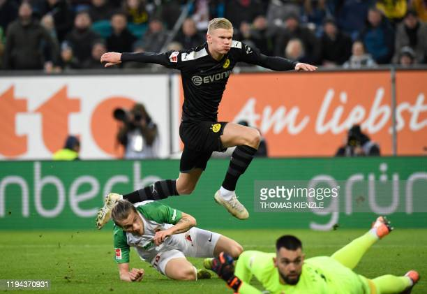 Dortmund's Norwegian forward Erling Braut Haaland jumps over Augsburg's Czech goalkeeper Tomas Koubek and Croatian defender Tin Jedvaj after he...