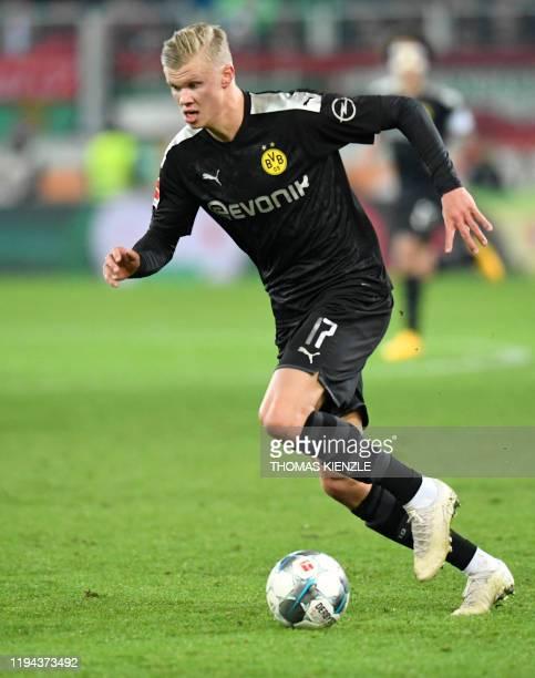 Dortmund's Norwegian forward Erling Braut Haaland runs with the ball during the German first division Bundesliga football match Augsburg v Borussia...