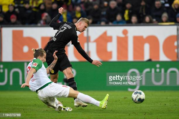 Dortmund's Norwegian forward Erling Braut Haaland scores the 23 past Augsburg's Croatian defender Tin Jedvaj during the German first division...