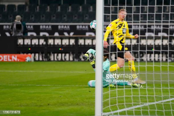 Dortmund's Norwegian forward Erling Braut Haaland scores the equalising goal 1:1 against Moenchengladbach's Swiss goalkeeper Yann Sommer during the...