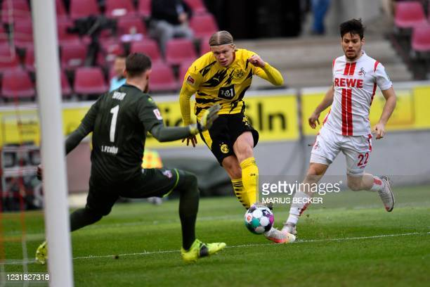 Dortmund's Norwegian forward Erling Braut Haaland scores the opening goal against Cologne's German goalkeeper Timo Horn during the German first...
