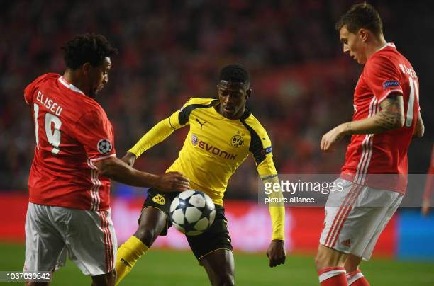 Dortmund's Ousmane Dembele and Lisbon's Victor Lindeloef and Eliseu vie for the ball during a Champions League round of 16 soccer match between SL...