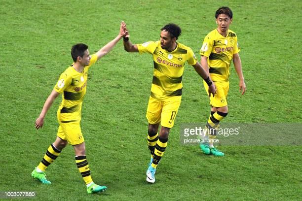 Dortmund's PierreEmerick Aubameyang celebrates his 12 penalty goal with teammates Christian Pulisic and Shinji Kagawa during the German DFBCup...