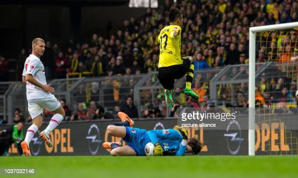 Dortmund's PierreEmerick Aubameyang in action against Augsburg's goalkeeper Marwin Hitz and Ragnar Klavan during the Bundesliga soccer match between...
