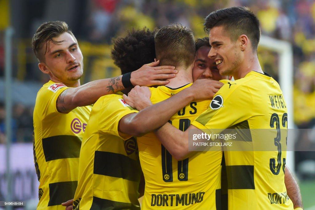 Dortmund's players celebrate after scoring during the German first division Bundesliga football match Borussia Dortmund vs Bayer Leverkusen, in Dortmund, western Germany, on April 21, 2018. (Photo by Patrik STOLLARZ / AFP)