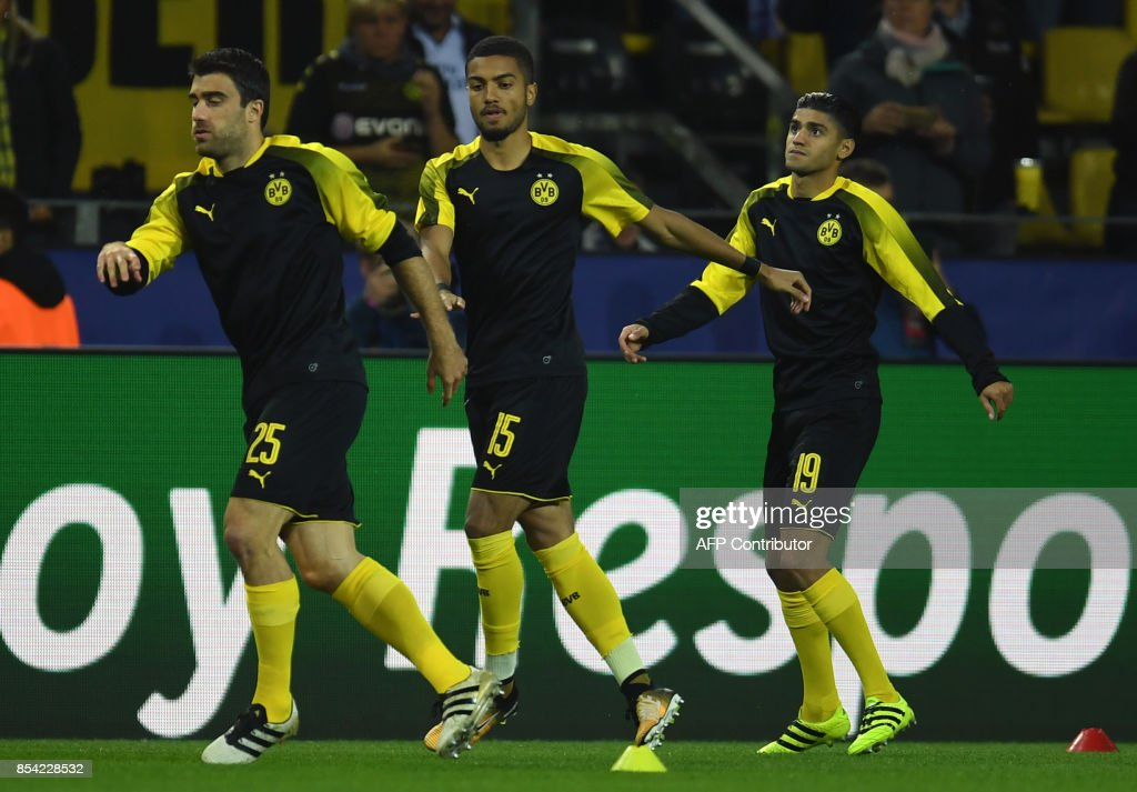 Dortmund's players (L-R) Greek defender Sokratis German defender Jeremy Toljan and German midfielder Mahmoud Dahoud warm up prior to the UEFA Champions League Group H football match BVB Borussia Dortmund v Real Madrid in Dortmund, western Germany on September 26, 2017. / AFP PHOTO / Patrik STOLLARZ