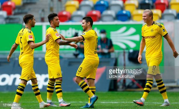 Dortmund's Portuguese defender Raphael Guerreiro celebrates with his teammates scoring a goal before it was ruled out by VAR during the German first...