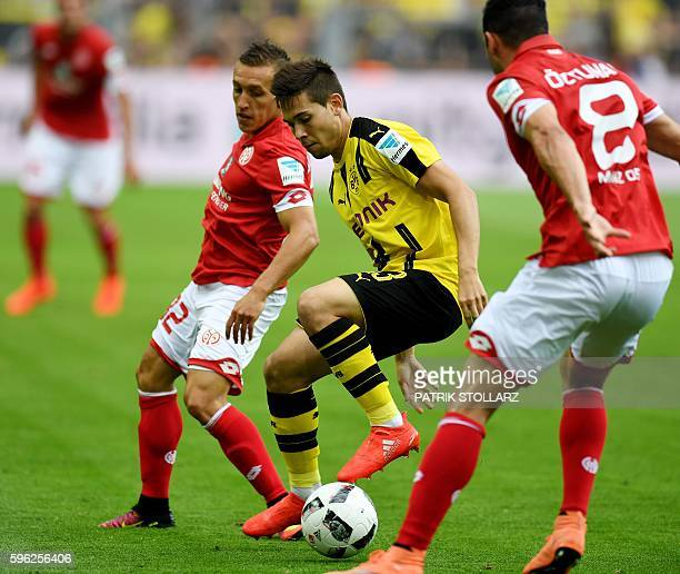 Dortmund's Portuguese defender Raphael Guerreiro vies for the ball with Mainz' Argentinean striker Pablo De Blasis during the German first division...