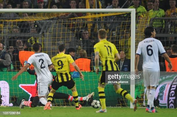 Dortmund's Robert Lewandowski scores 21 goal against Madrid's goalkeeper Diego Lopez and Raphael Varane during the UEFA Champions League semi final...