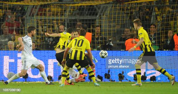 Dortmund's Robert Lewandowski scores 31 goal against Madrid's goalkeeper Diego Lopez and Xabi Alonso during the UEFA Champions League semi final...