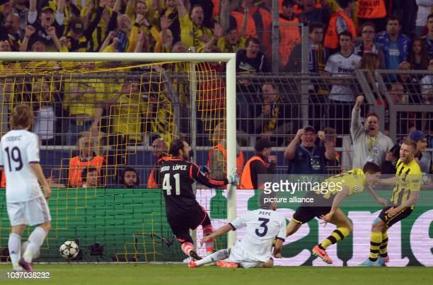 Dortmund's Robert Lewandowski scores the opening goal against Madrid's goalkeeper Diego Lopez next to Dortmund's Jakub Blaszczykowski during the...