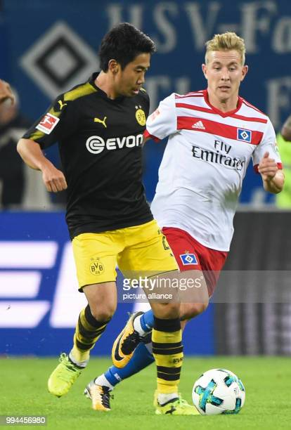 Dortmund's Shinji Kagawa and Hamburg's Lewis Holtby vie for the ball during the German Bundesliga soccer match between Hamburger SV and Borussia...