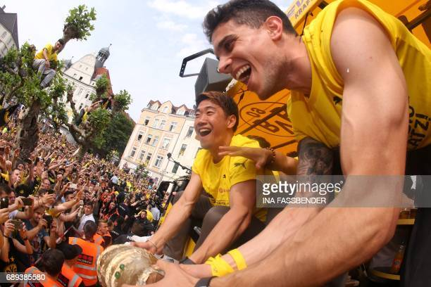 Dortmund's Spanish defender Marc Bartra and Dortmund's Japanese midfielder Shinji Kagawa celebrate withfans as they arrive at Borsigplatz during...