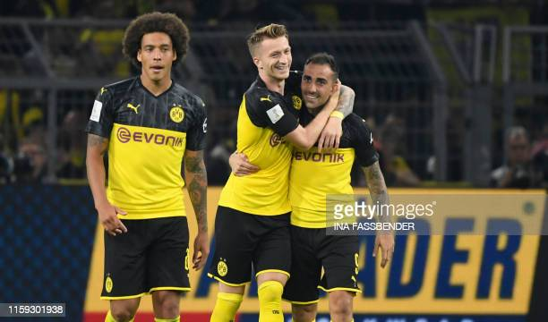 Dortmund's Spanish forward Paco Alcacer celebrates scoring the opening goal with his teammates German forward Marco Reus and Belgian midfielder Axel...