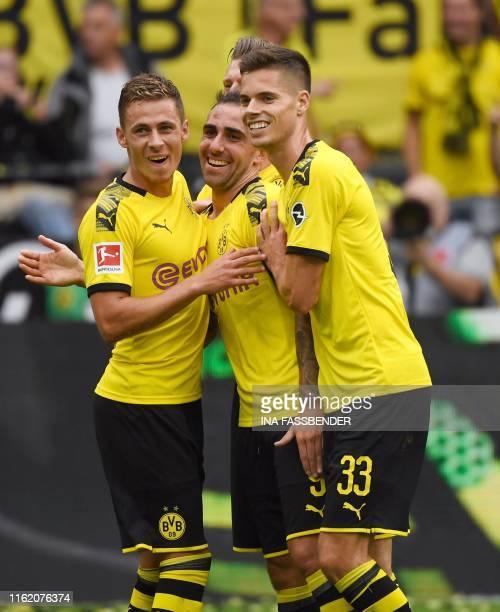 Dortmund's Spanish forward Paco Alcacer celebrates scoring with his team-mates Belgian forward Thorgan Hazard and German midfielder Julian Weigl...