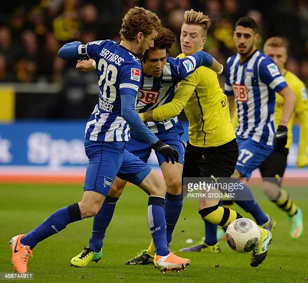 Dortmund's striker Marco Reus Hertha's Swiss midfielder Fabian Lustenberger and Hertha's Japanese midfielder Hajime Hosogai vie for the ball during...