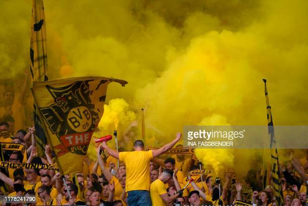 Dortmund's supporters light pyrotechnics during the German First division Bundesliga football match between Schalke 04 and Borussia Dortmund in...
