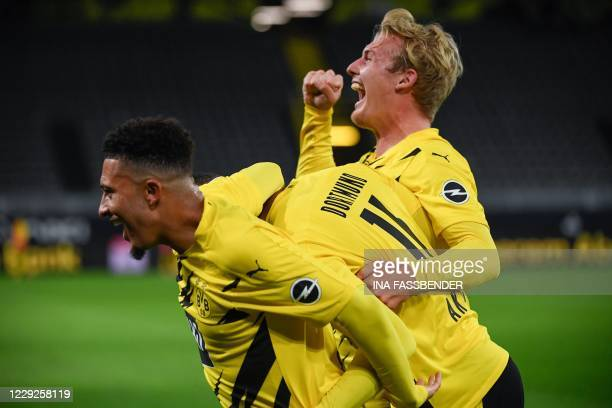Dortmund's Swiss defender Manuel Akanji celebrates scoring the opening goal with his teammates Dortmund's English midfielder Jadon Sancho and...