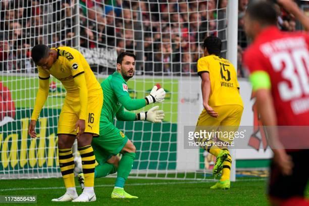 Dortmund's Swiss defender Manuel Akanji Dortmund's Swiss goalkeeper Roman Buerki and Dortmund's German defender Mats Hummels react after an own goal...