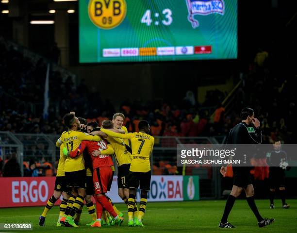 Dortmund's Swiss goalkeeper Roman Buerki celebrates with his teammates after the penalty shoot-out of the German Cup DFB Pokal round of 16 football...