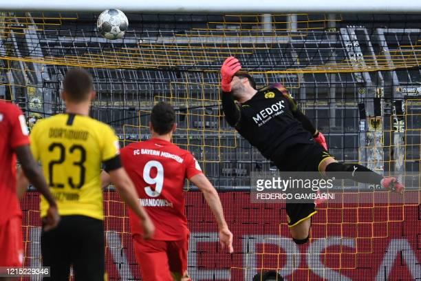 Dortmund's Swiss goalkeeper Roman Buerki fails to keep out the opening goal scored by Bayern Munich's German midfielder Joshua Kimmich during the...