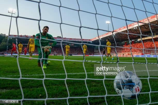 Dortmund's Swiss goalkeeper Roman Buerki watch the ball in the net after Union Berlin's German forward Marius Buelter scored the opening goal during...