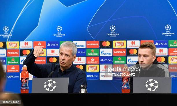Dortmund's Swiss head coach Lucien Favre and Dortmund's German forward Marco Reus address a press conference on October 23 2018 in Dortmund on the...