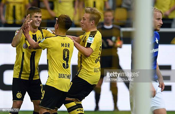 Dortmund's Turkish midfielder Emre Mor is congratulated by teammates after scoring during the German first division Bundesliga football match of...
