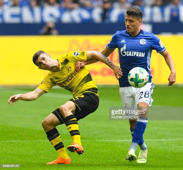 Dortmund's US midfielder Christian Pulisic and Schalke's Austrian midfielder Alessandro Schoepf vie for the ball during the German first division...