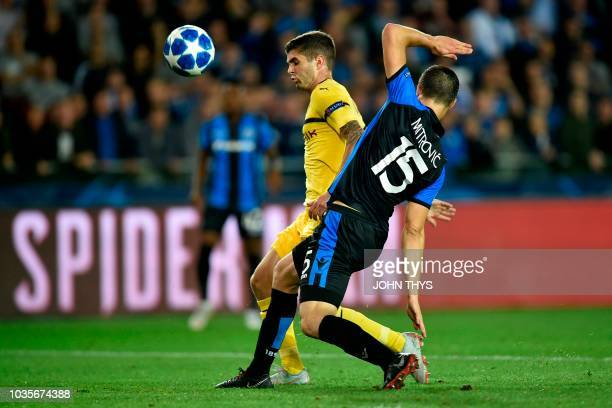 Dortmund's US midfielder Christian Pulisic scores past Club Brugge's Croatian defender Matej Mitrovic during the UEFA Champions League Group C...