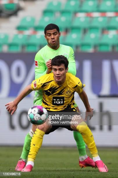 Dortmund's US midfielder Giovanni Reyna and Wolfsburg's Brazilian defender Paulo Otavio vie for the ball during the German first division Bundesliga...
