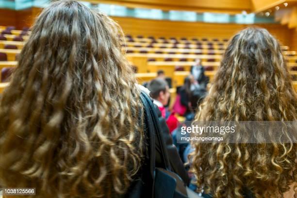 dos estudiantes jóvenes escuchan la presentación del senado - welliges haar stock-fotos und bilder
