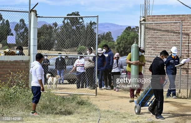 Dos hombres ingresan a la planta de oxígeno medicinal del Valle en la plabacion de Arbieto, para recargar sus cilindros, en las afueras de Cochabamba...
