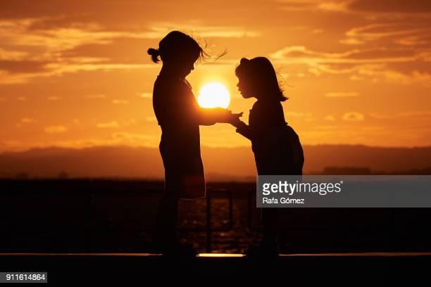 Dos niñas agarradas de la mano con la puesta de sol