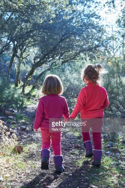 Dos niñas caminan de la mano por el bosque en el parque de Cabañeros.