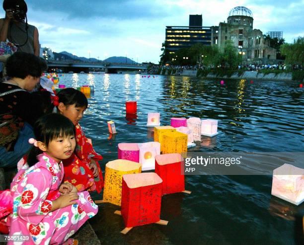 Dos ni?as vestidas con trajes t?picos depositan linternas flotantes en el r?o Motoyasu frente al monumento Bomba A Domo, en el Parque del Memorial de...