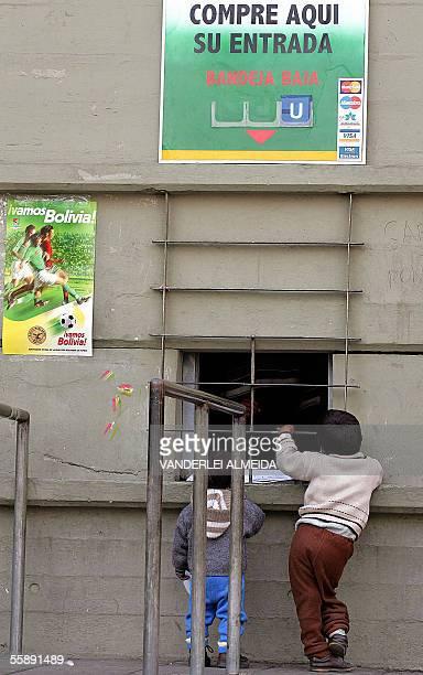 Dos ninos conversan con los vendedores de una de las boleterias del estadio Hernando Siles en La Paz el 07 de octubre de 2005 donde Bolivia y Brasil...