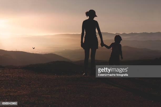 Dos siluetas de personas mirando un paisaje de montañas