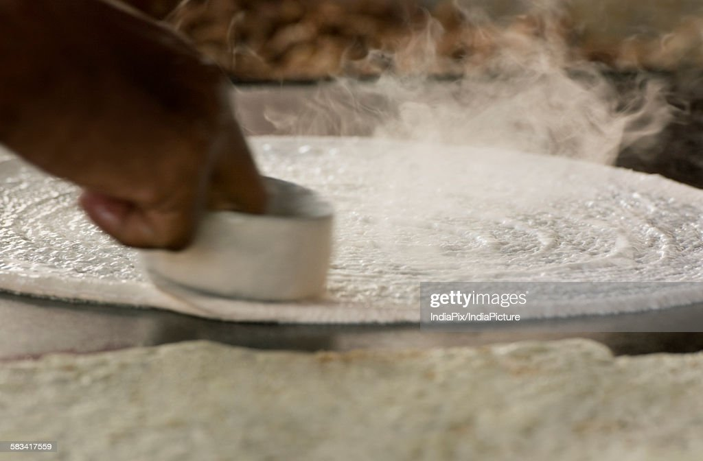 Dosa batter being spread on tawa : Stock Photo
