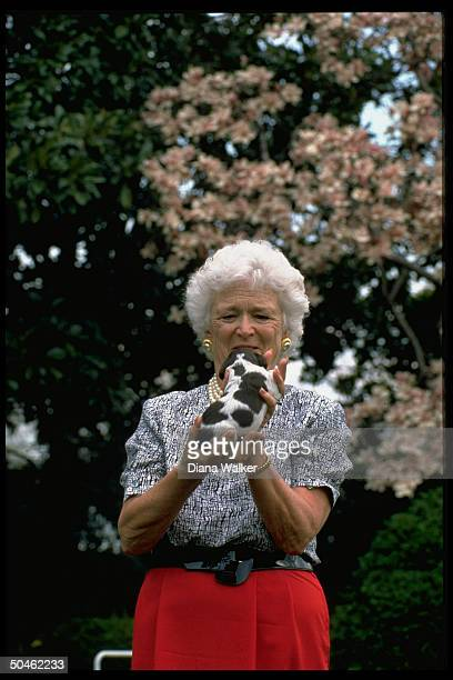 Doting signature pearls sporting Barbara Bush holding one of family dog Millie's new puppies on WH grounds