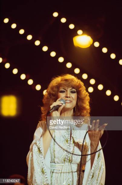 Dottie West US country music singersongwriter singing into a microphone during a live concert performance circa 1980