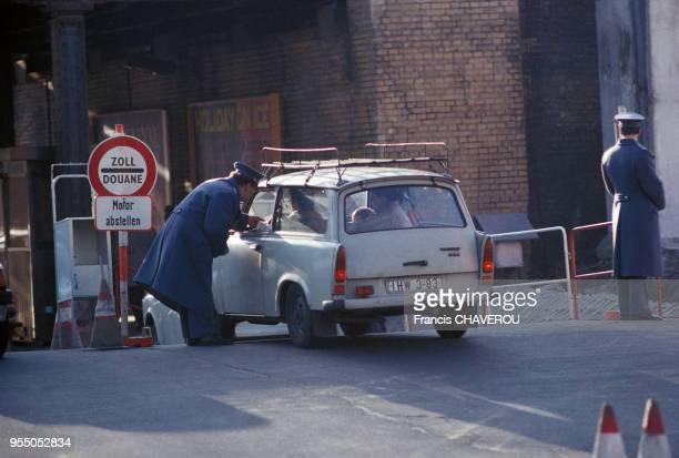 Douanier contrôlant une voiture à un checkpoint du côté est du Mur de Berlin en février 1990 Allemagne