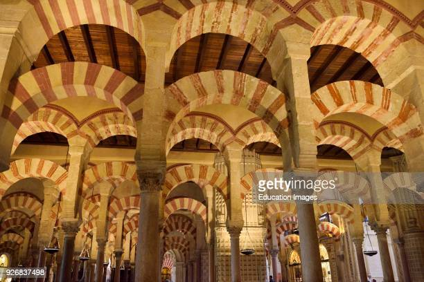 Double arches of white stone and red brick at the Hypostyle Prayer Hall in the Cordoba Cathedral Mosque