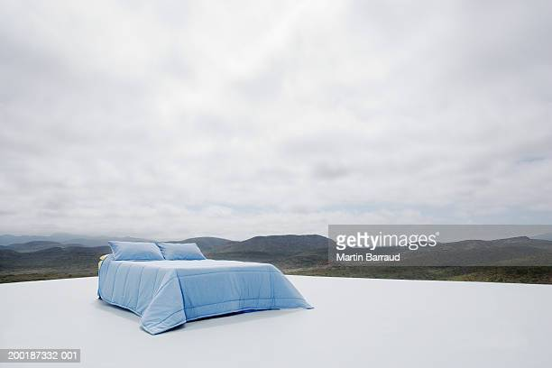 Double bed on platform overlooking rugged landscape