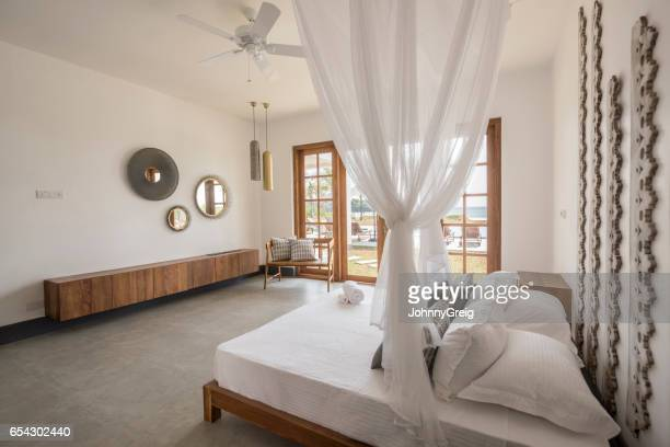 double bed with mosquito net and contemporary furniture - mosquito net stock photos and pictures