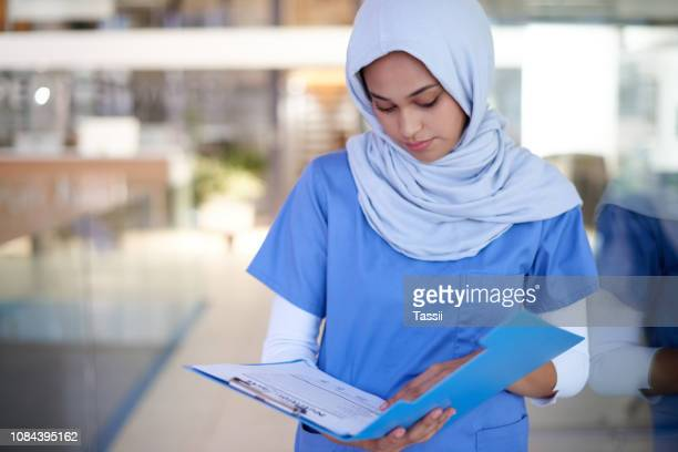 double checking her patient's details - medical chart stock pictures, royalty-free photos & images