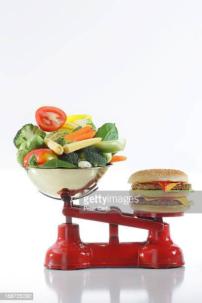 double cheese burger and vegetables on red scales - scale stock pictures, royalty-free photos & images